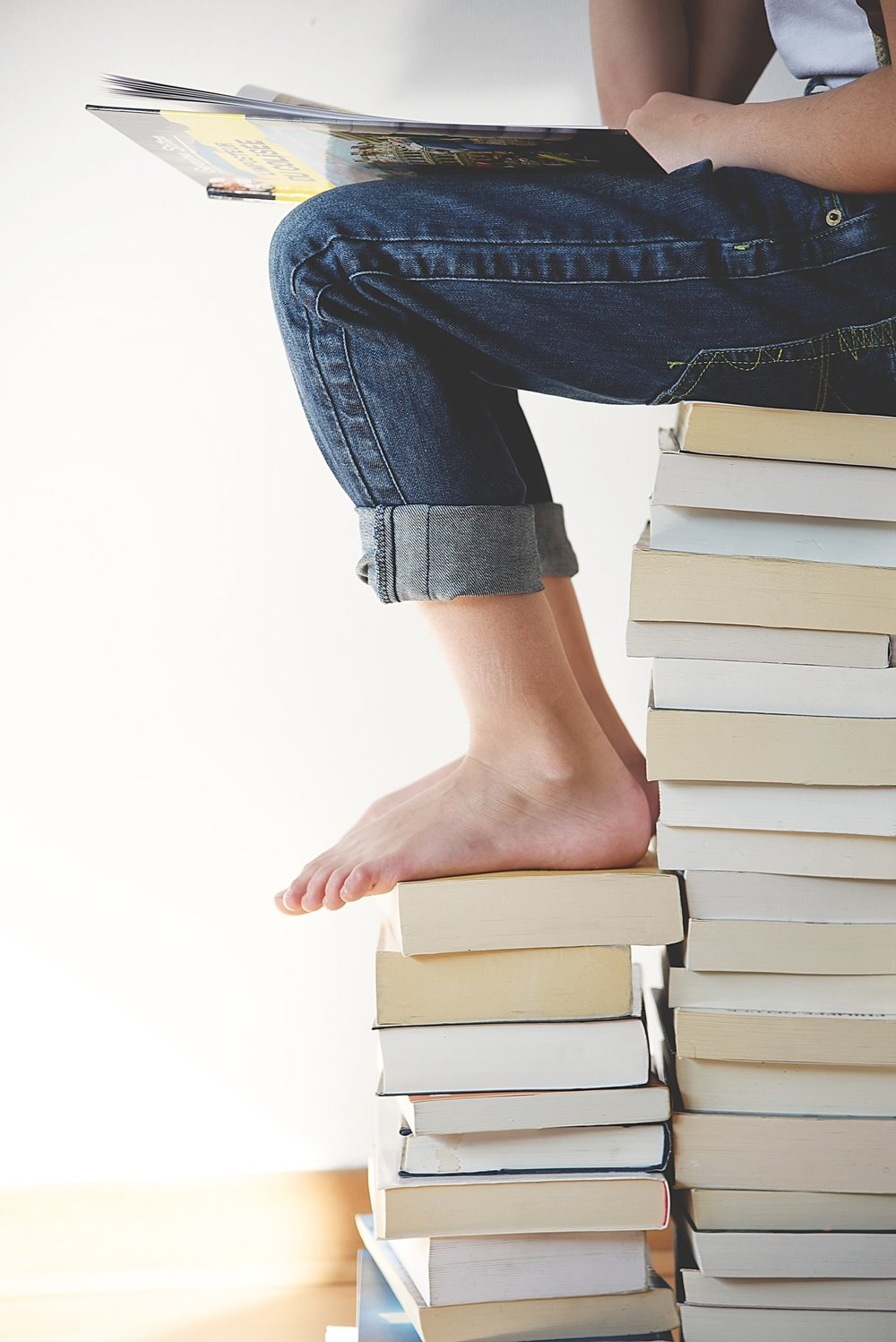 unsplash girl reading sitting on books.jpg