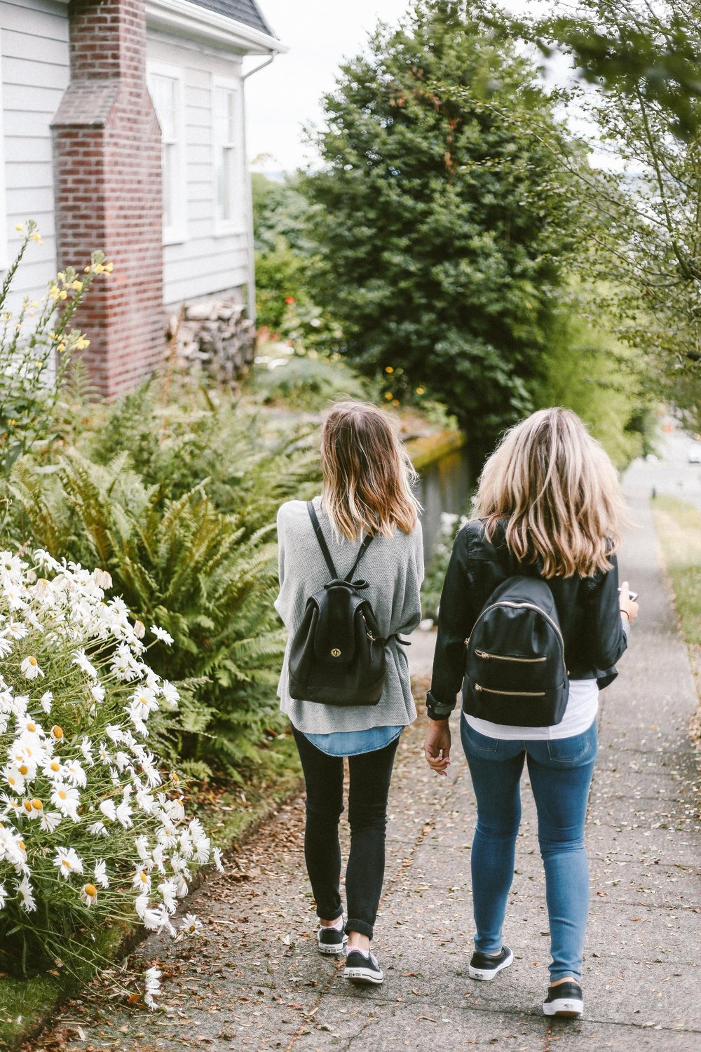 unsplash girls backpacks walking away.jpg