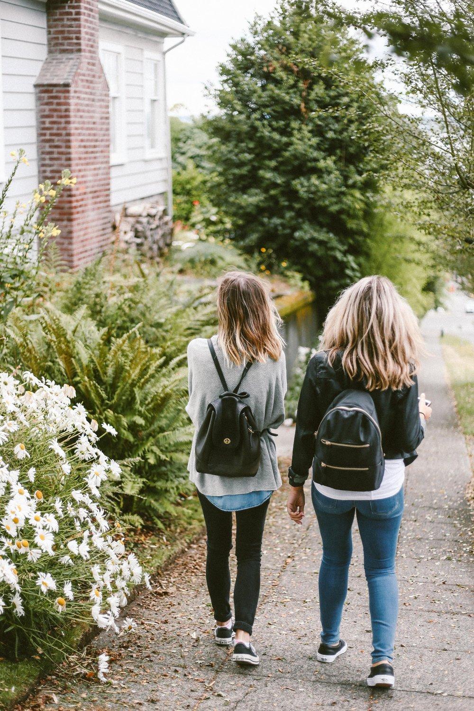 unsplash girls backpacks walking away.jpg