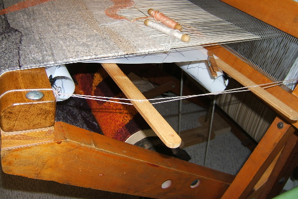 Cartoon support with lease sticks on counter balance rug loom.  Note how the cartoon is rolled near the front beam, as well as near the beater.     © 2017 Elizabeth J. Buckley photo