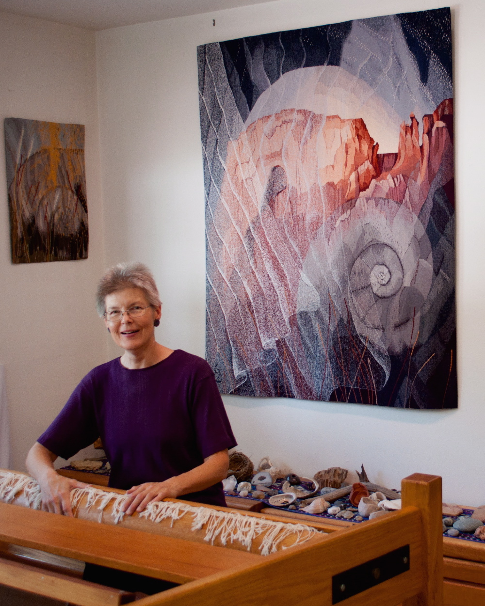 "Elizabeth J. Buckley in her studio.  Tapestries behind:  The Veils of Time     60"" x 50   ©2017  ;  Fossil, Feather, and Light  25"" x 18""   ©2013   Photo credit:  Nancy Wohlenberg"