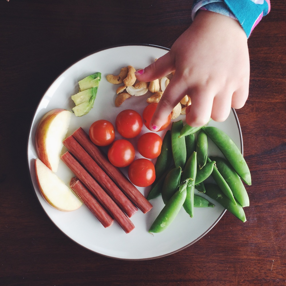 Grass-fed beef sticks, sugar snap peas, cherry tomatoes, apple slices, avocado slices and cashews.