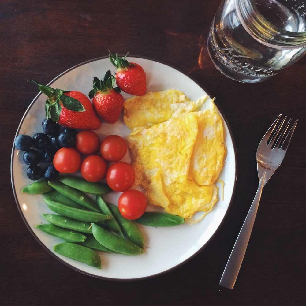 Scrambled eggs cooked in coconut oil, cherry tomatoes, sugar snap peas, blueberries and strawberries.