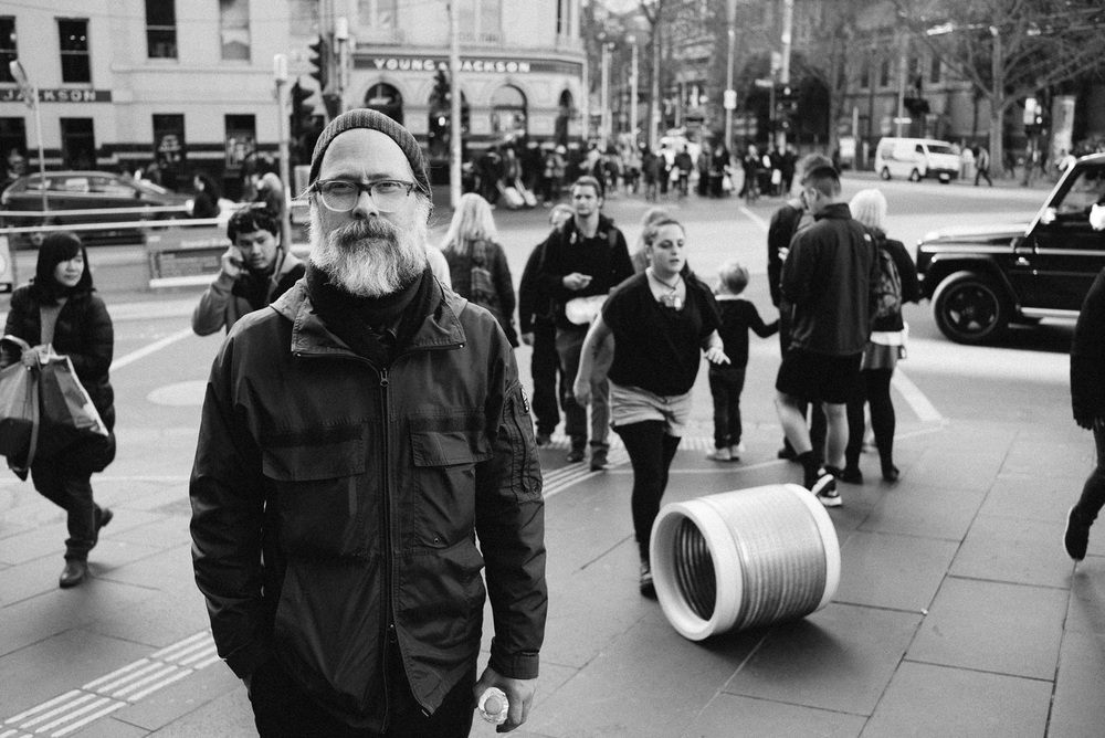 Simon and a woman rolling a barrel out the front of Flinders Street Station.