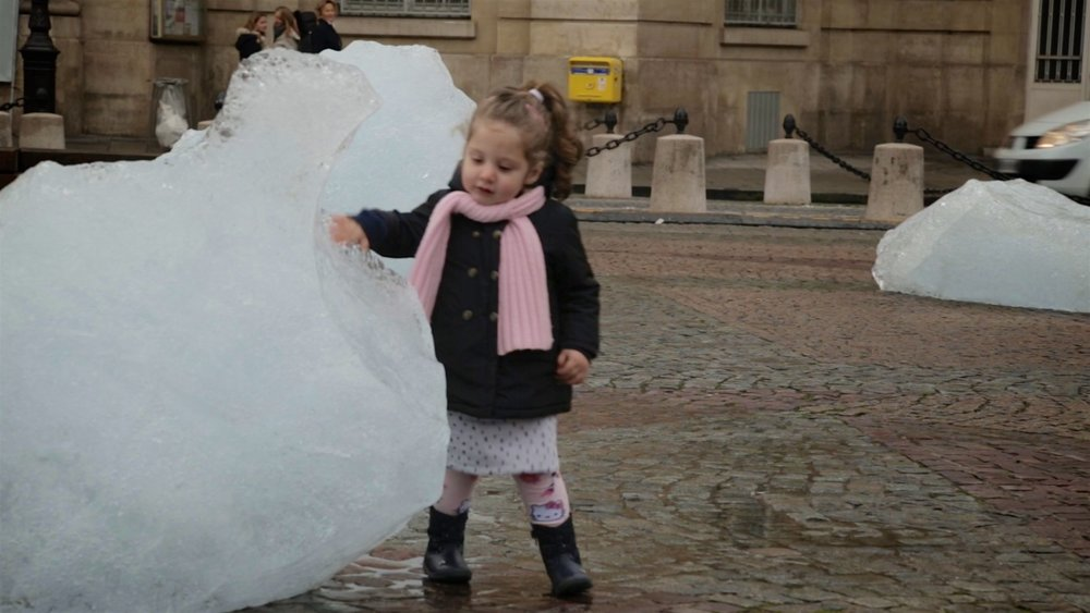 Girl touches melting ice from Arctic glacier at COP21 Paris.jpg