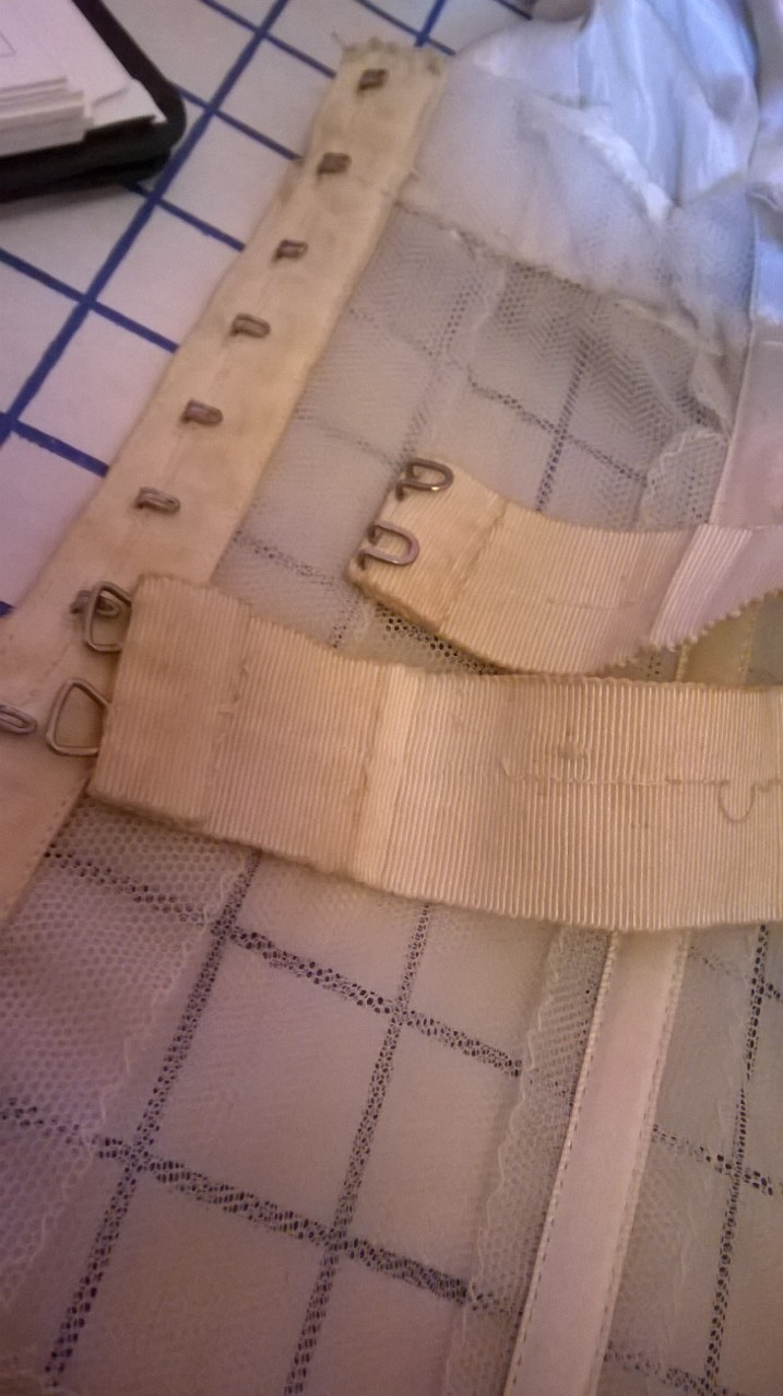 This shows the ribbon channels, the separately hooked waist tape and the hand overcasting on the seam allowances.