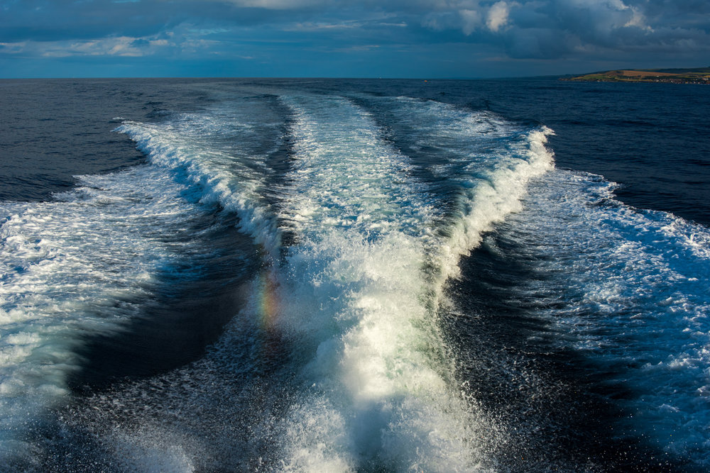 The wake of the Trent class all-weather lifeboat. The engine is so powerful that it has created a fine mist that, as the sun is low and strong, has refracted the light and we see a small rainbow.