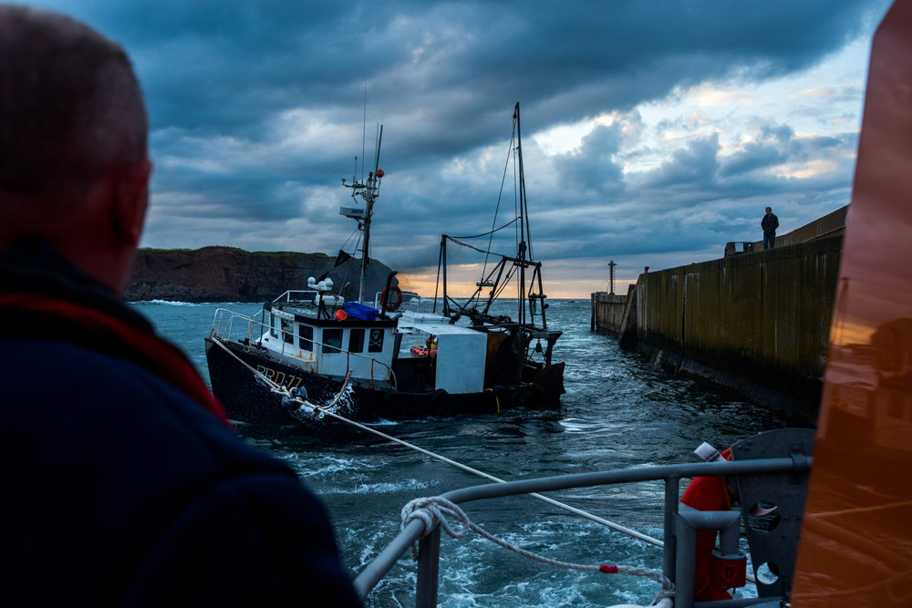 "A moment of held breaths as the captain of 'Our Catherine' accelerates to try to avoid plowing in to the harbour wall but too much as he almost crashes into the other side. A crewmember steps in front of me and tells me, ""The line might snap"". The in-shore D class lifeboat can be seen through the fishing boat's tent tied to the rear to act as a makeshift rudder."