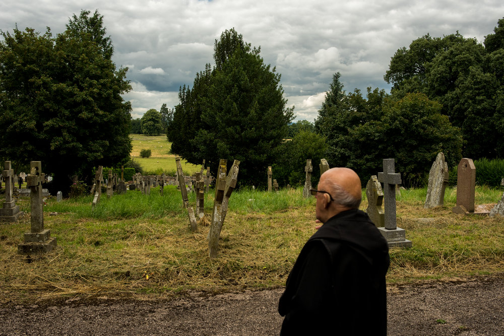 Father Cadfan looks out over the monk graveyard. He is given the role of a tour guide, showing people round Belmont Abbey, Hereford, England 2016