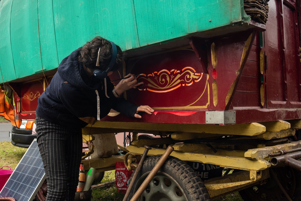 With three practices inside the wagon and one on some scrap wood, Bryony feels comfortable painting her first scrolls