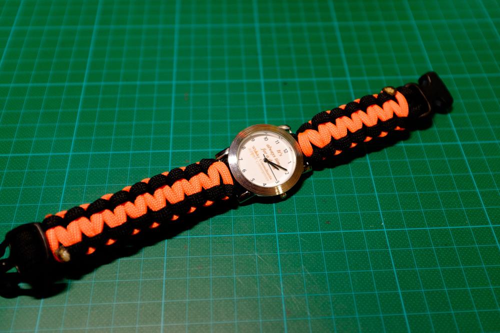 Die Jubiläumsuhr (5 Jahre) der Whisky Consultants mit einem in ihren Farben geknüpften Armband (Salomon Bar).