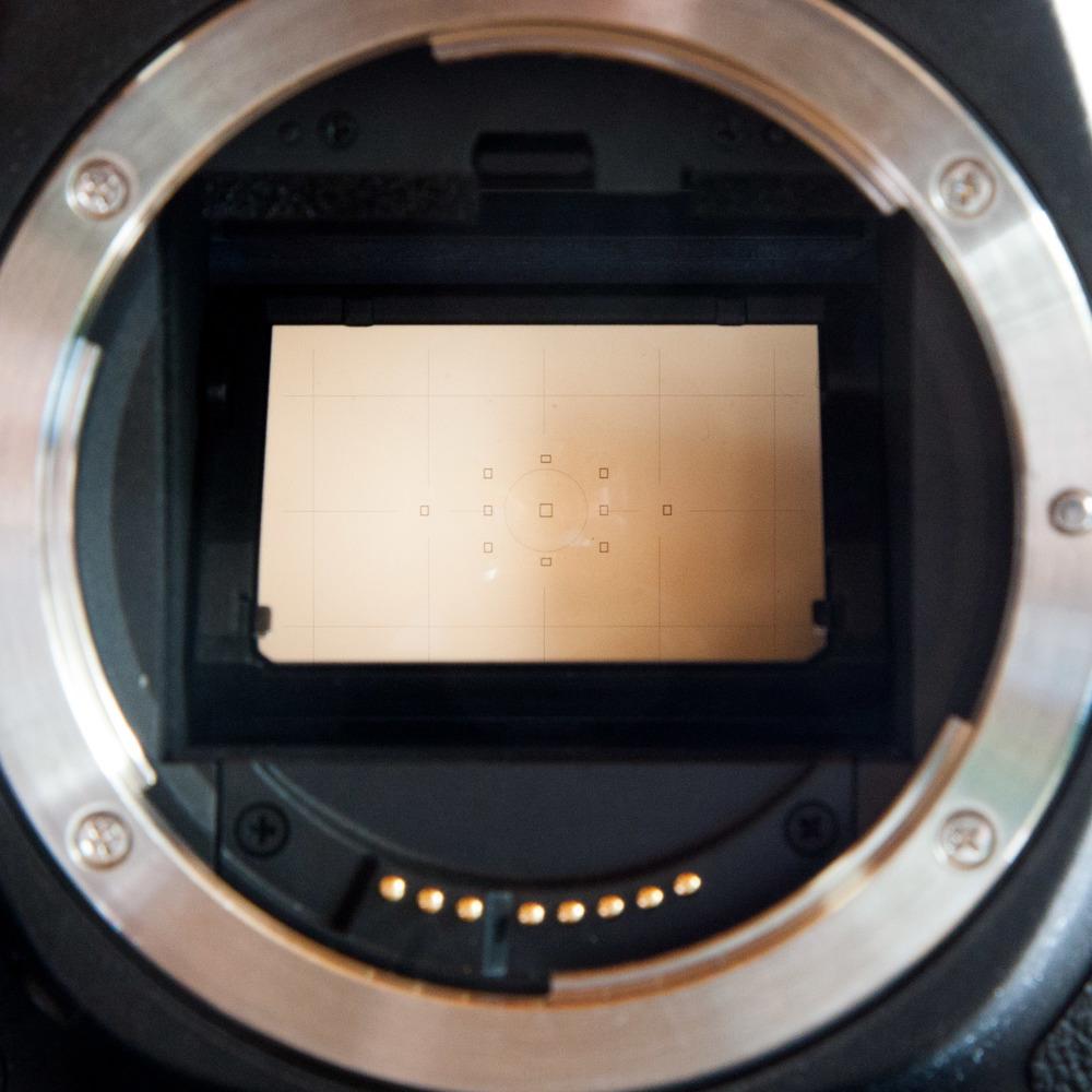 Das Herzstück der SLR - der Spiegel der das vom Objektiv kommende Licht zum Sucher umleitet. Die Gravuren auf der Mattscheibe sind deutlich erkennbar.