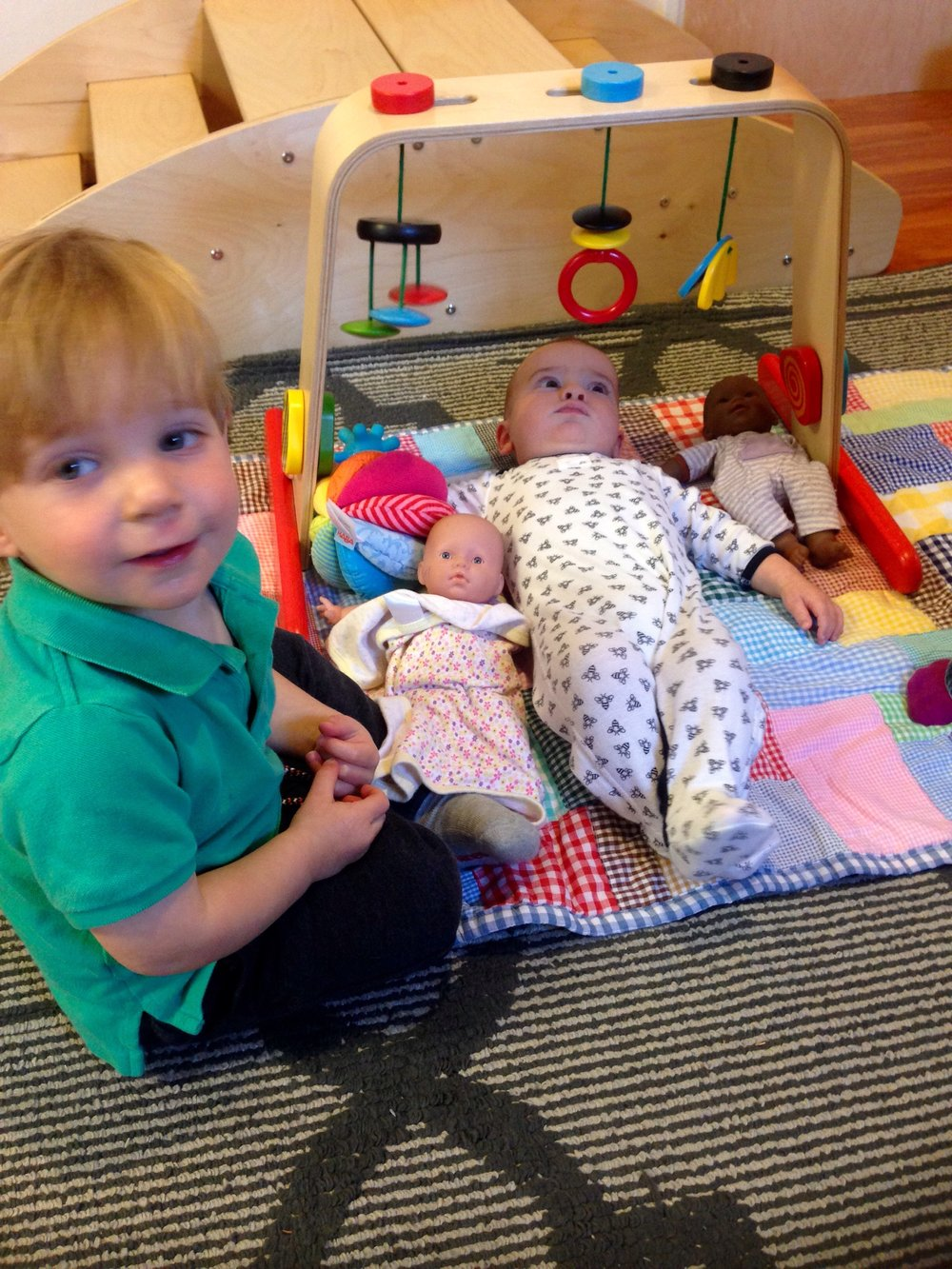 Baby with dolls in toddler room Nido Durham