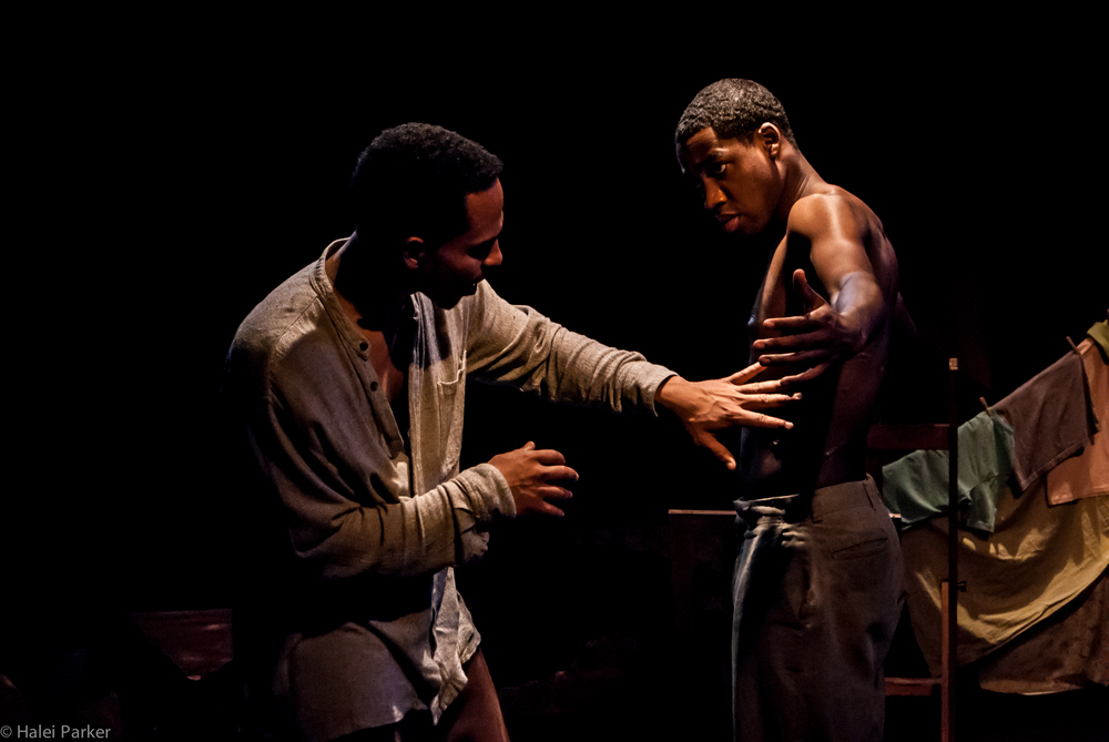 Edwin (Gerard Joseph) touches the scars that Henri-Max (Maurice Williams) got while being tortured by Duvalier's boogiemen.
