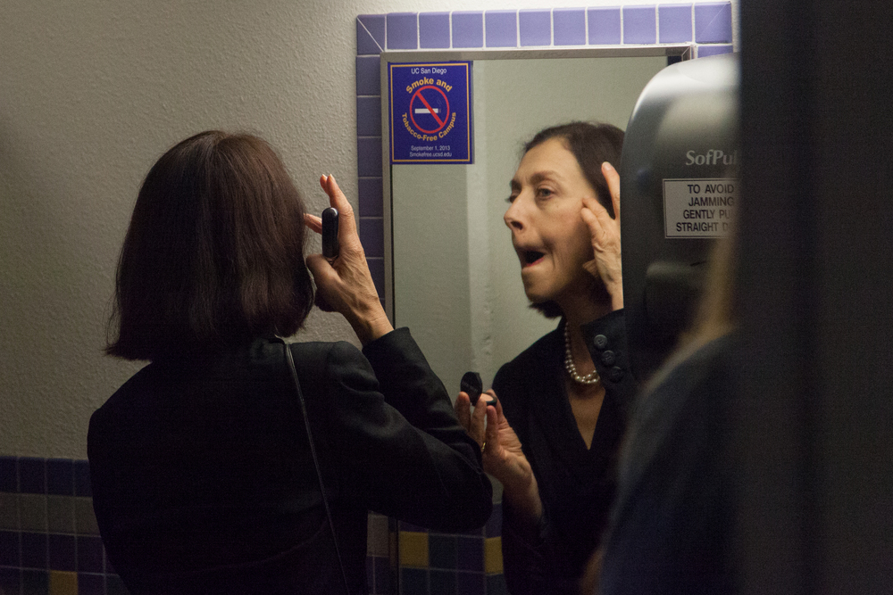 Gertrude (Eva Barnes) gives beauty advice to the audience in the bathroom.