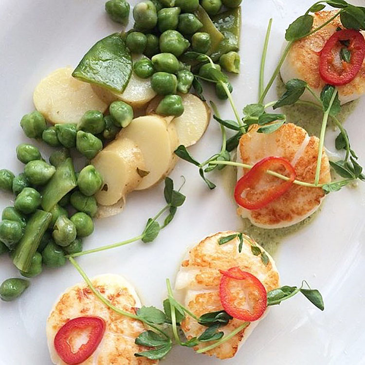 Seared Montauk sea scallops with fingerling potatoes, green chick peas, corrander crema and pickled fresno chilies