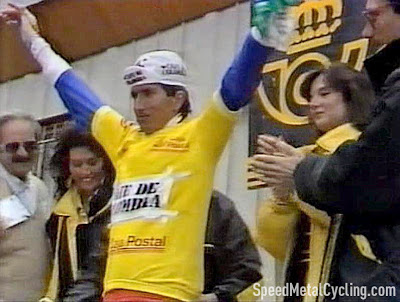 Lucho Herrera went up to the podium to receive the first of what would eventually be 11 Yellow Jerseys, with Sean Kelly 39 seconds back in second, Dietzen third at 50 seconds. Note that the Café de Colombia logo is on a printed piece of paper attached to the jersey with masking tape. Real classy.