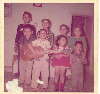 Desde muy pequeño supe que en la música iba a encontrar la manera de hacer sonreír a la gente.   Aquí estoy en el centro tocando la guitarra, a mi derecha mi hermano Raymundo riéndose de mis ocurrencias. A mi izquierda, mi única hermana: Xóchitl y mi Hermano Luis Ignacio, recién llegados de Michoacán .  En la parte de atrás una familia muy querida de Camargo, Tamps.