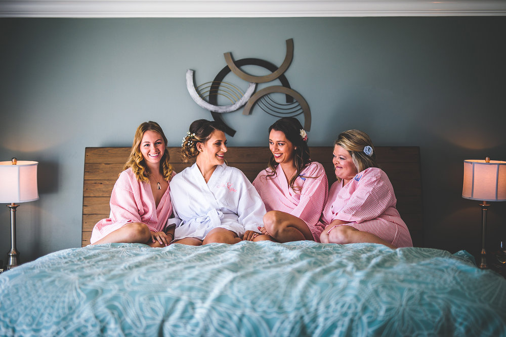 bridesmaids laughing on a bed.jpg