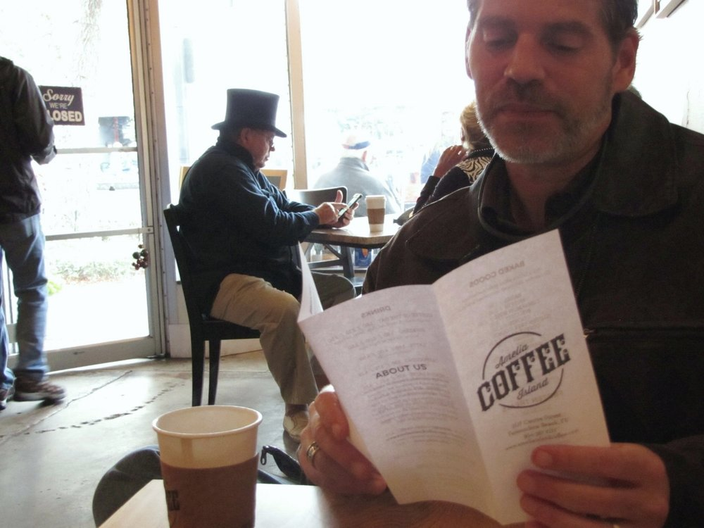 men with menu and top hat in coffee shop