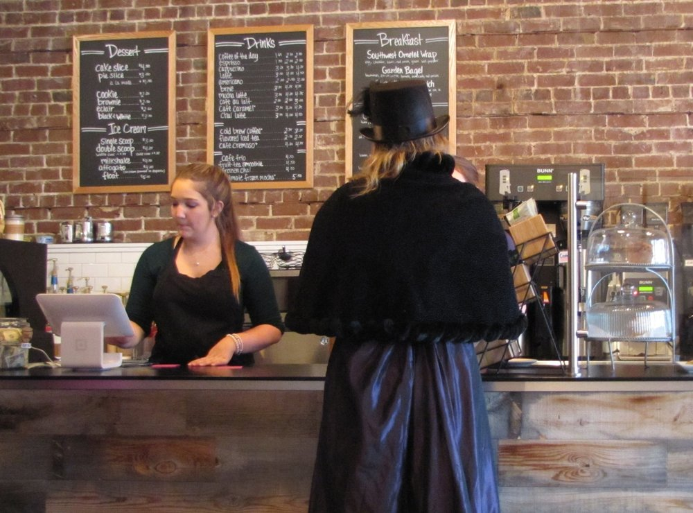 woman in historic costume in modern coffee shop