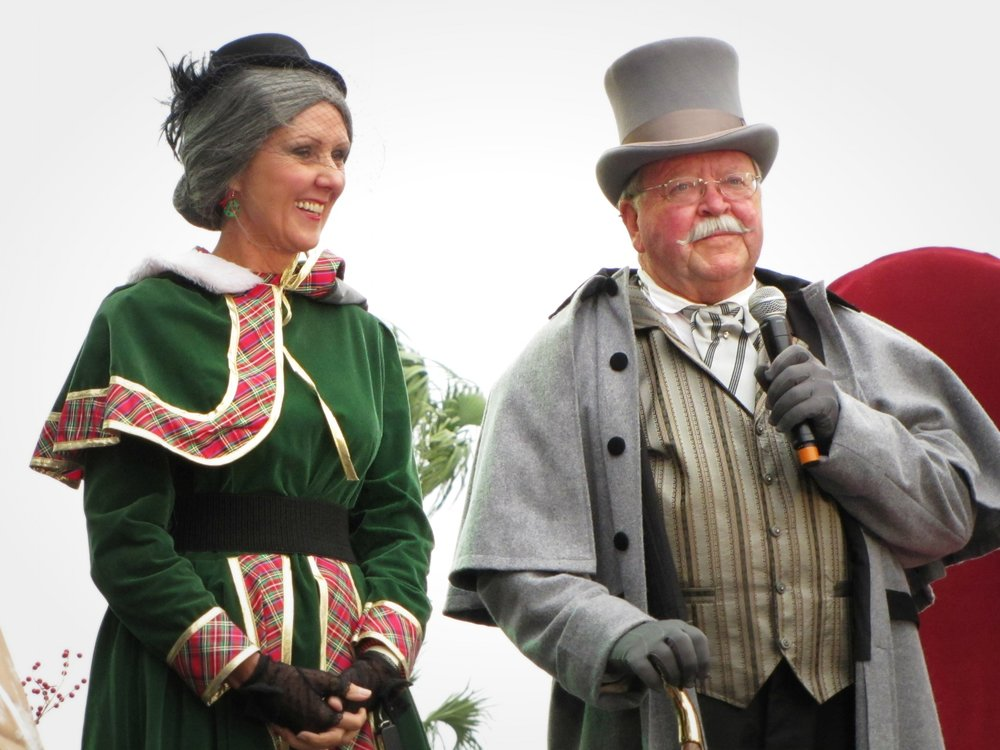 woman dressed as mrs. clause and man dressed in top hat and cloak