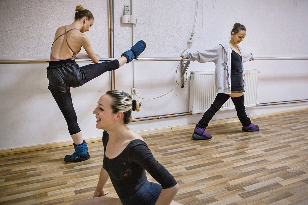 Three members of the new generation of The Kosovo Ballet get warmed-up before rehearsal in the training room.