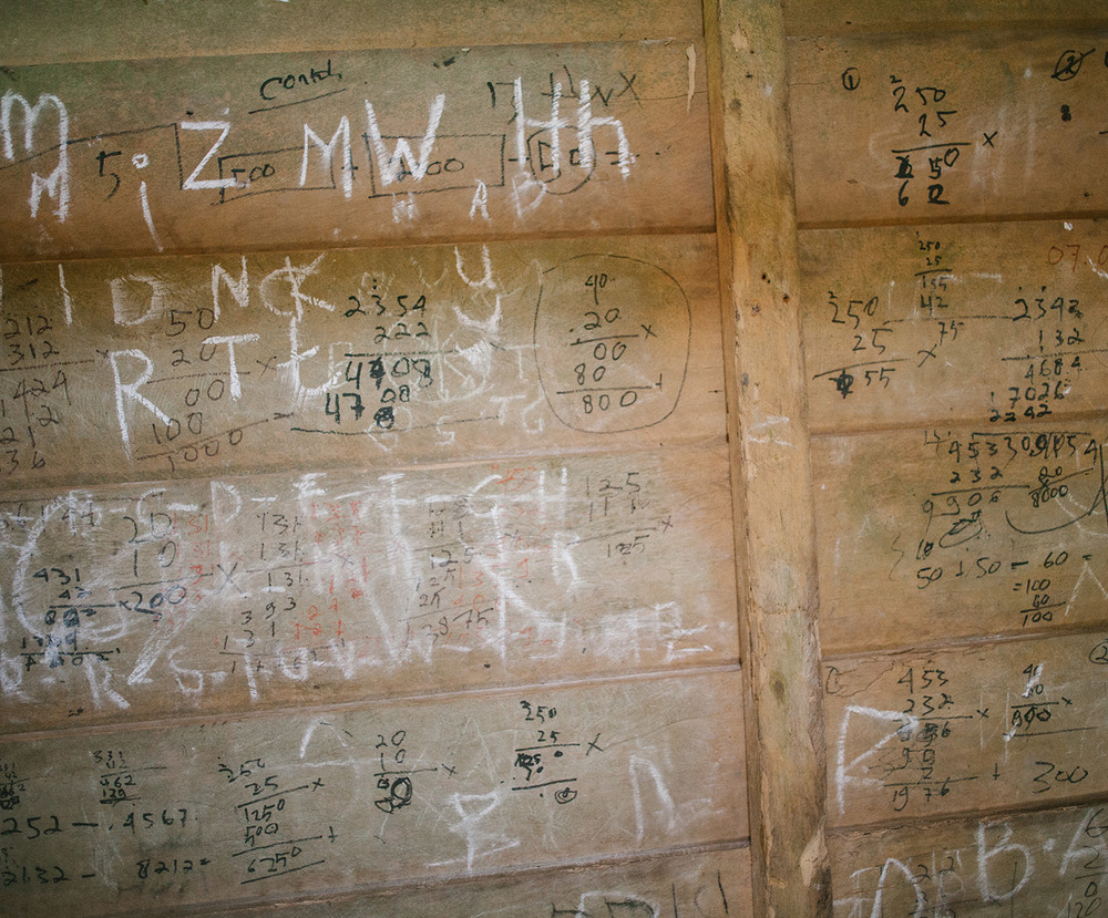 Students' writing on the wall of a jungle school, Buttui.