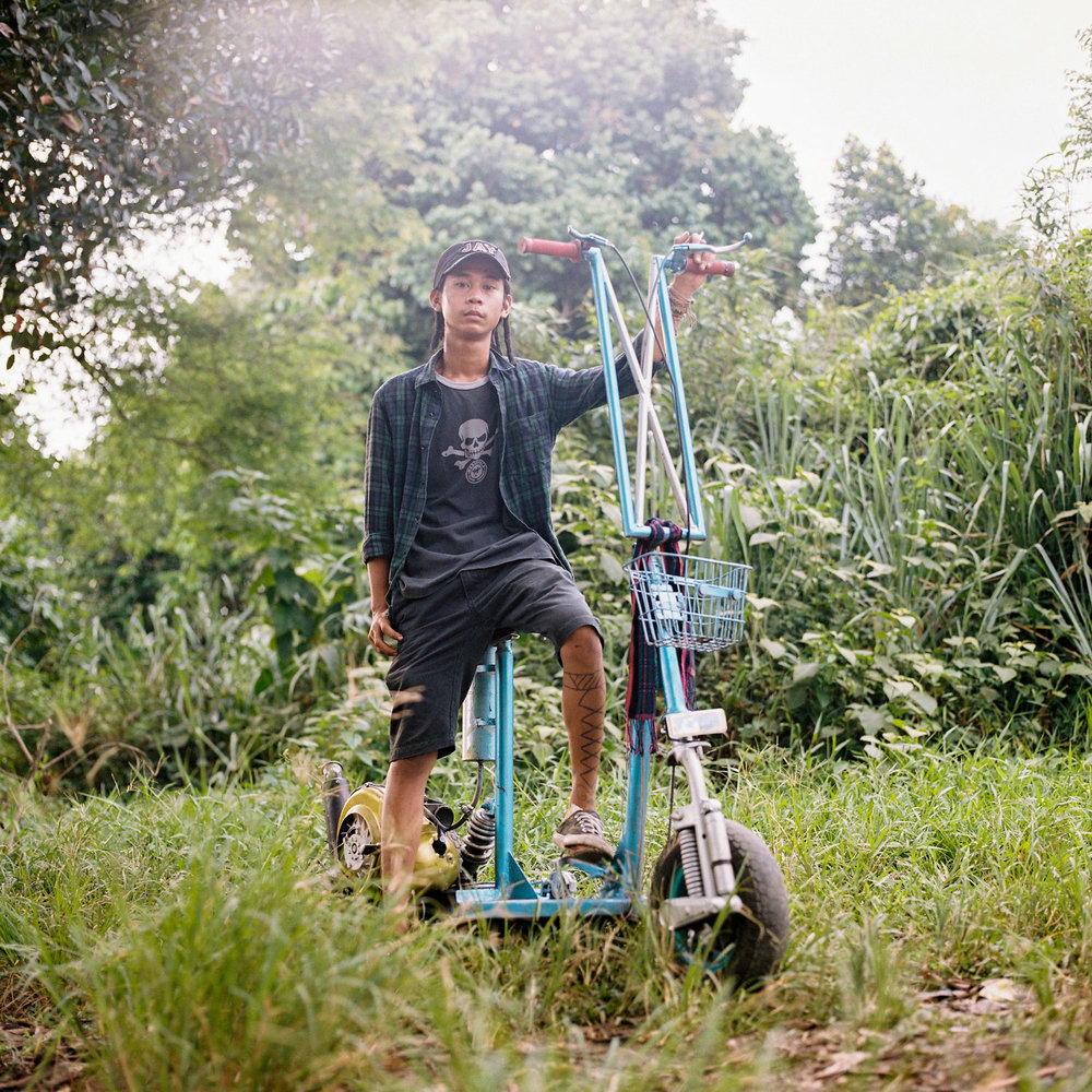 Bonjay, a scooterist from Jakarta, posed for a portrait with his kick scooter style vespa.