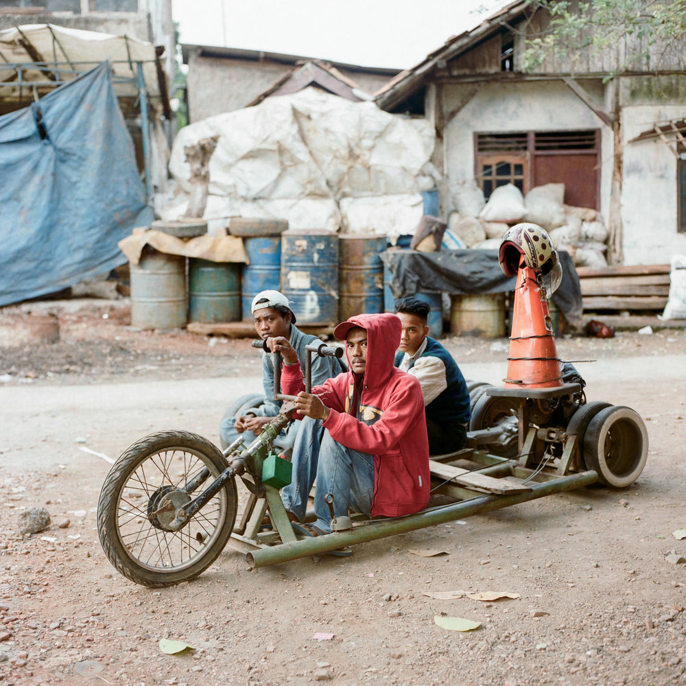 Three scooterists, Adul (middle), Bango (left), and Ajis (right), posed for a portrait with their custom-made lowrider vespa in Bekasi, a sprawling Jakarta suburb.