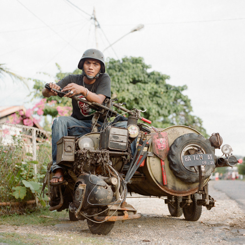 Sugik, a scooterist from Padang, West Sumatra, posed for a portrait onboard his modified vespa built from used oil drum and iron bars. As an experienced mechanic, he pushed the boundaries further by installing two engines for more power and custom-made reverse gear.