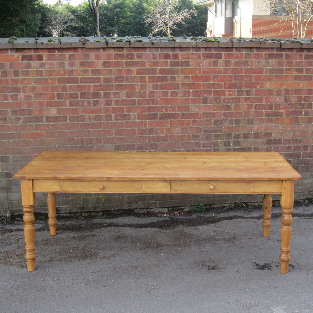large pine table with turned legs and 2 drawers in the side