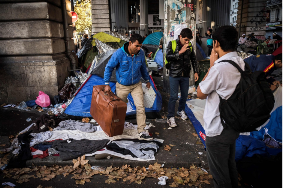 A migrant carrying his belongings at camp on Boulevard de la Villette in northern Paris.   Credit Lionel Bonaventure/Agence France-Presse — Getty Images