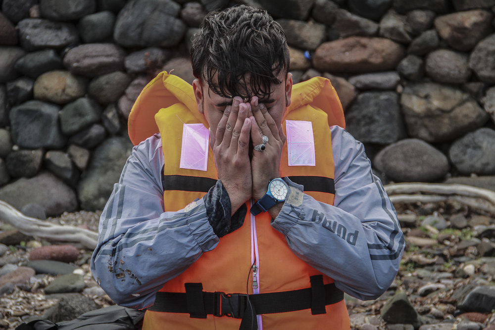 A Syrian refugee sinks to his knees moments after arriving safely to the shores of Lesvos. The boat that left before his never made it and at least another 33 refugees drowned in the Aegean that day. October 2015.