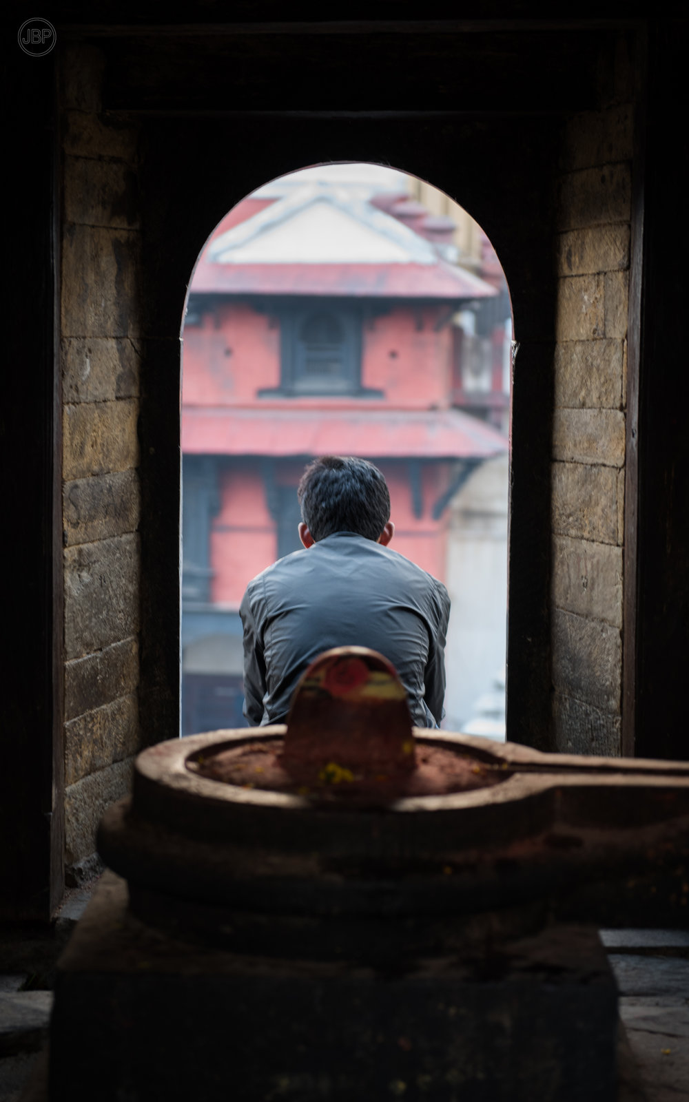 Man sits in the window of a Hindu shrine