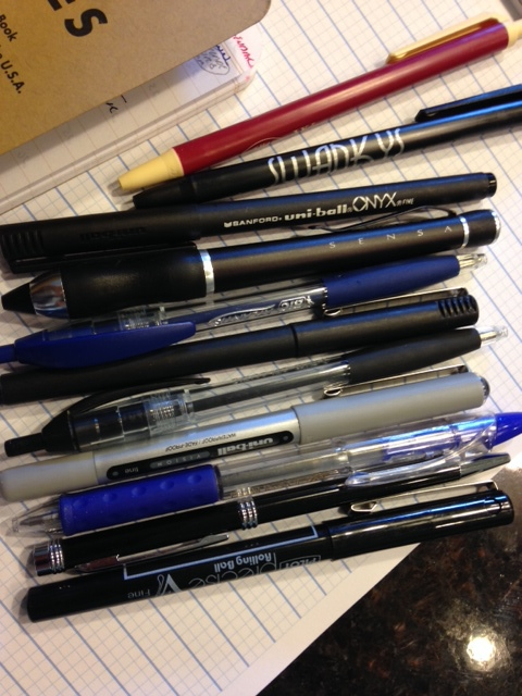 The pens, not the Field Notes.  From top:  2 Bic clic stics, Sanford Uni-Ball Onyx (fine), Sensa X400 Rollerball, Bic Atlantis ballpoint in blue, Sanford Uniball Micro, Bic Atlantis ballpoint in black, Uniball Vision Fine, Pentel RSVP RT, junk hotel ballpoint, and Pilot Precise V7.