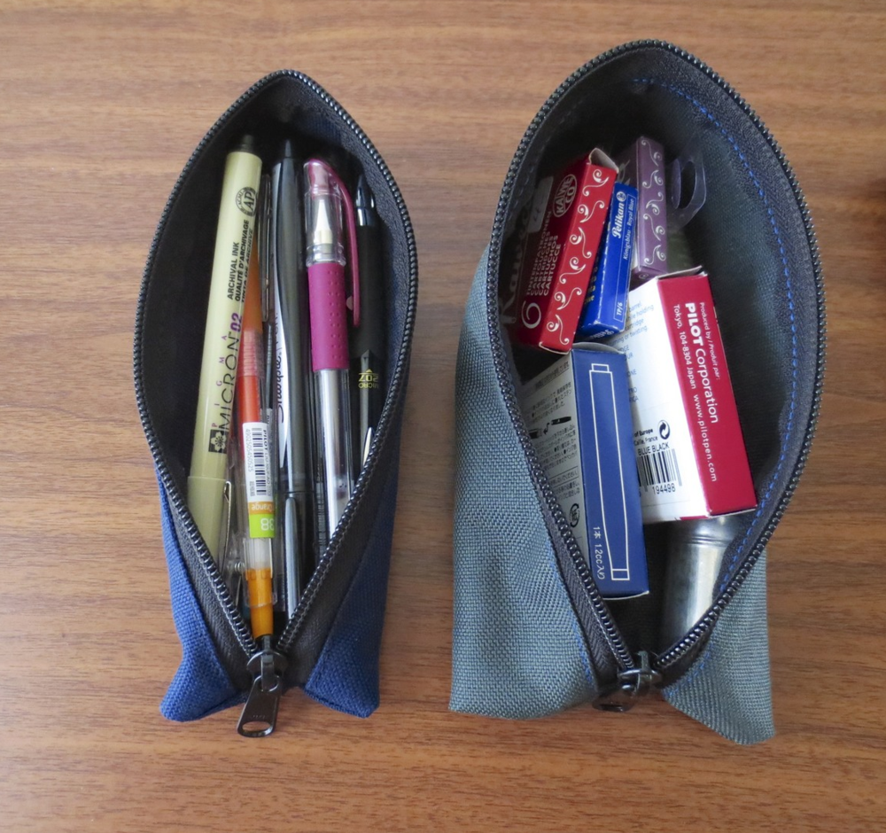 Small Chimneytop in Midnight, on the left; Large Chimneytop in Steel, on the right.  A wide variety of pens fit into these cases.  Pictured are the Sakura Pigma Micron, Pilot Juice, Signo DX, Signo 207, and Sharpie.