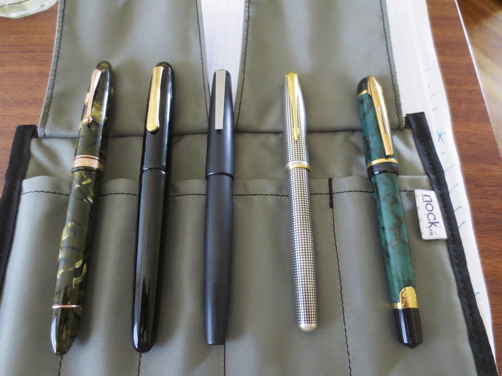 Pens from left:  (1) Omas Ogiva in Saft Green with Masuyama-ground medium nib, loaded with Iroshizuku Kon Peki (2) Nakaya portable writer with medium nib, loaded with Montblanc Alfred Hitchcock; (3) Lamy 2000 with Greg Minuskin retipped .9mm stub nib, loaded with Akkerman Voorhout Violet; (4) Parker Sonnet Cisele with Fine Nib, loaded with Aurora Black; and (5) Waterman Phileas with Medium Nib, loaded with Iroshizuku Yama Budo.