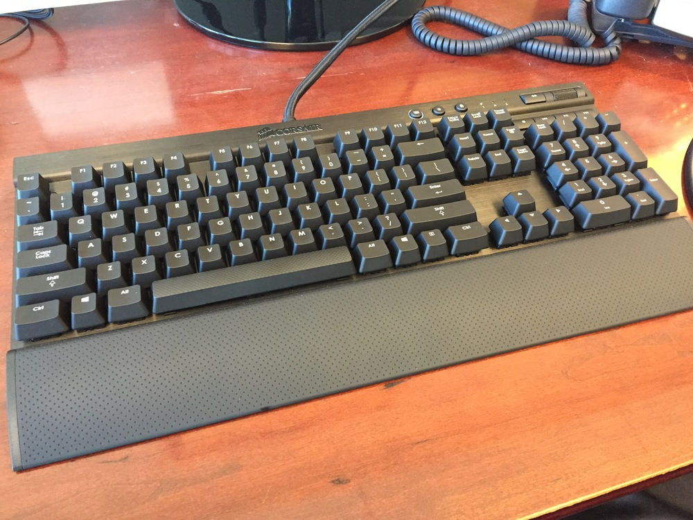 My Corsair K70 mechanical keyboard, on my desk at work.  The keyboard is much heavier than the Logitech Wave it replaced, and doesn't slide all over the place.  The wrist-rest is well-constructed and fits my hands/wrists perfectly.