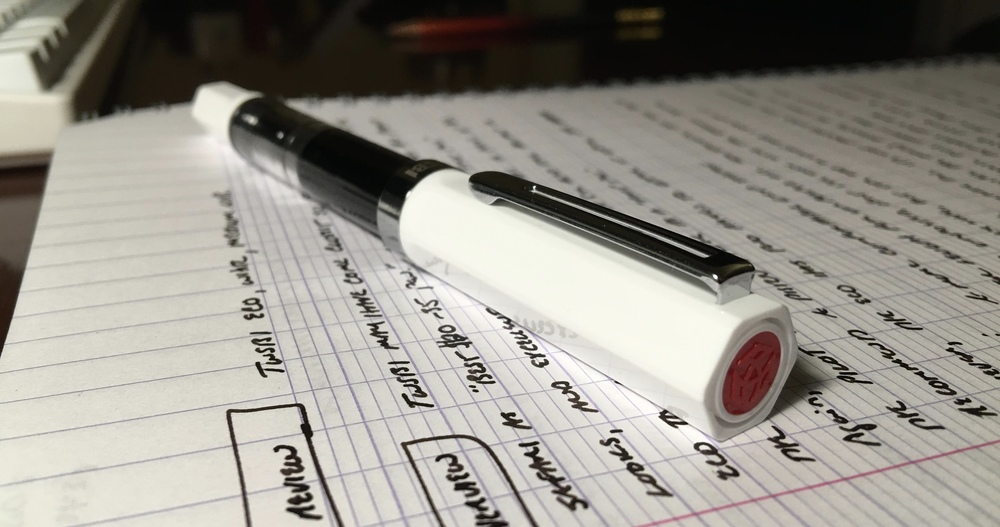 The TWSBI Eco, featured here in white, has a hexagonal cap with the red TWSBI dot.