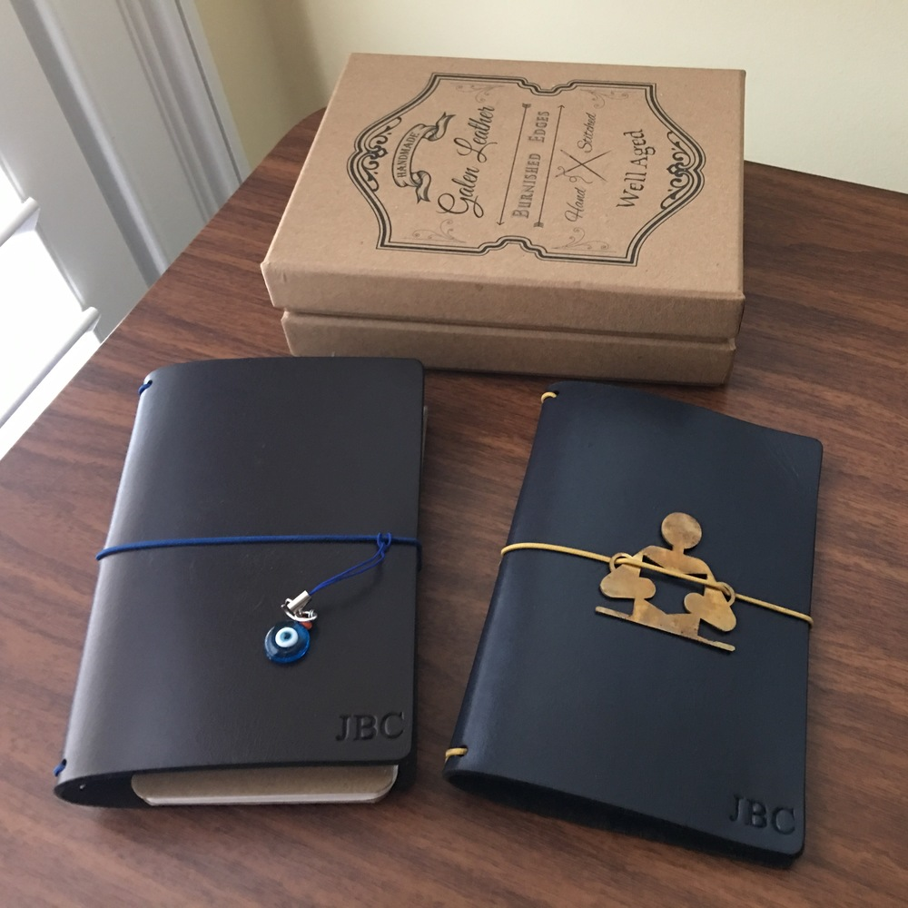"I left the brass charm on the blue notebook, but swapped out the charm on the brown for the ""evil eye"" talisman that comes with every Galen Notebook.  Here's some background on the meaning of the ""evil eye""."