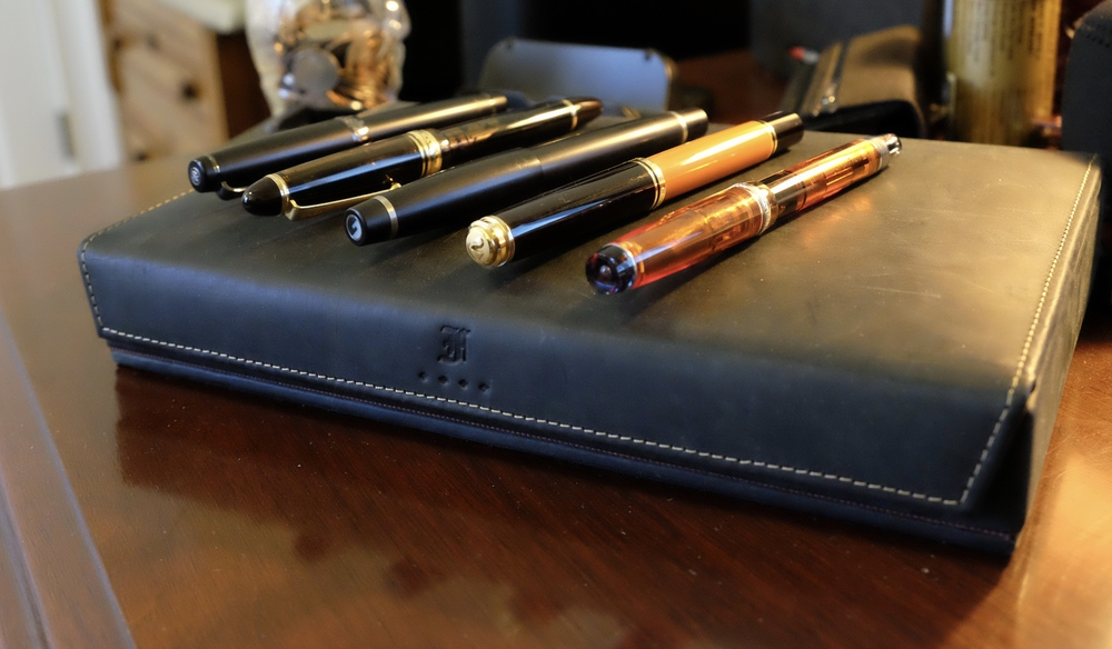 "One big goal of mine is to get to a point where the pens I consider my ""Tier Ones"" are always inked and available for me to write with.  From left, Sailor Pro Gear Imperial Black, Pilot Custom 823, Conid Bulkfiller Minimalistica, Pelikan M800 Burnt Orange, and Pilot Custom Heritage 92."