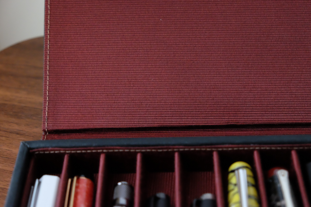 A close up look at the textured burgundy cloth used to line the Covered Pen Tray. It's durable while still being soft enough not to scratch your pens.