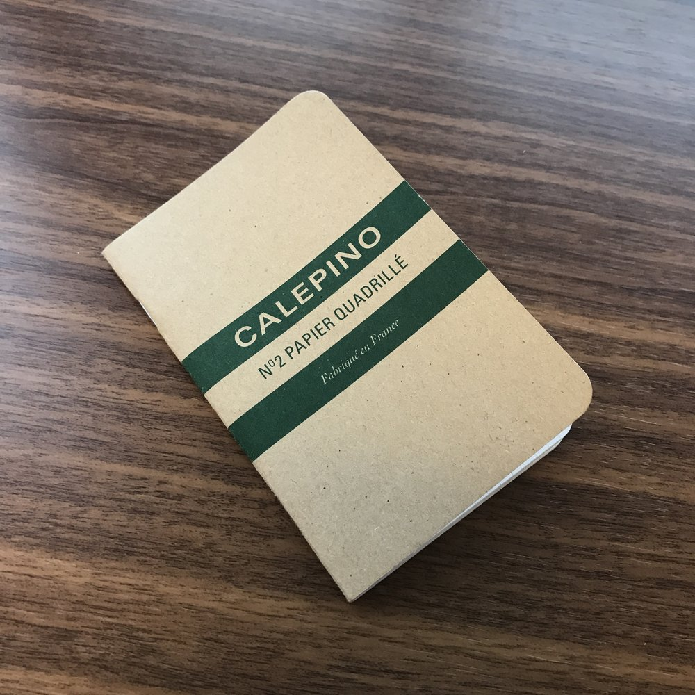 The standard Calepino cardboard-covered notebook. Graph-ruled notebooks have green trim, blank notebooks blue, and lined notebooks red. The dot grid notebooks are a light gray cardboard with light green trim.