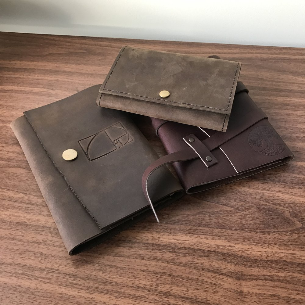 "From left, the medium Snap journal with the ""Golden Mean"" brand, the small Snap journal, and the Triple Wrap journal with the ""Tree of Life"" brand."