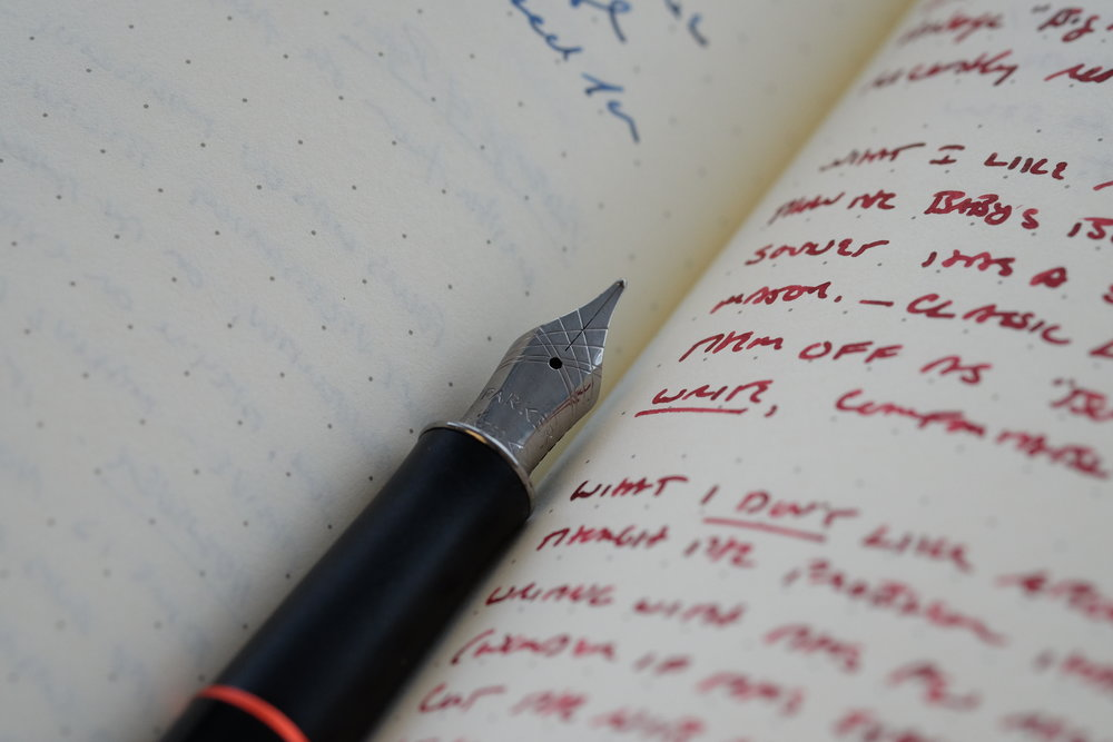The clip, section band, and nib are a darker nickel color, which blends nicely with the black and red color scheme.