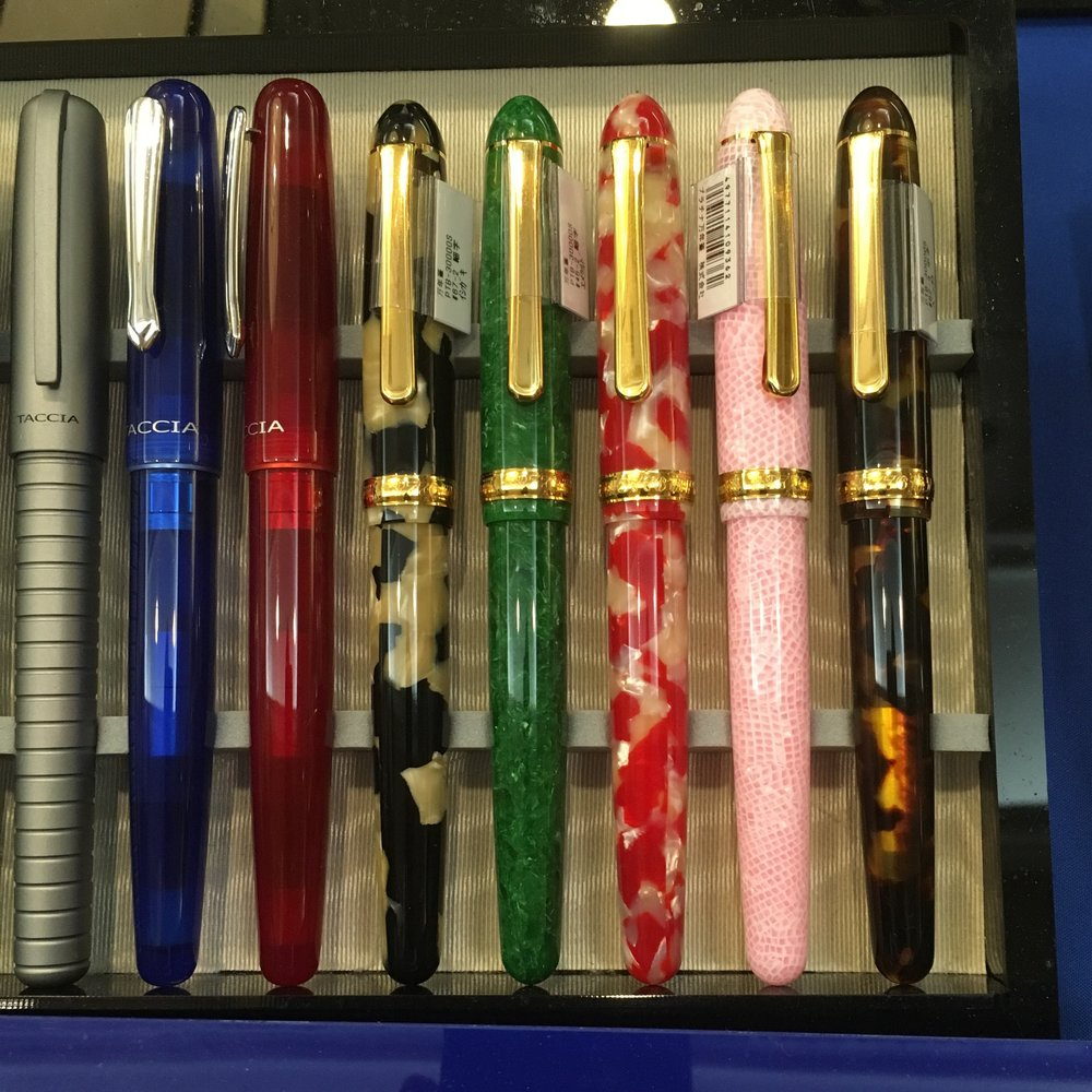 Taccia pens on display alongside some gorgeous celluloid Platinum 3776s at the Anderson Pens table at the 2017 D.C. Pen Show.  On the far left, the Taccia Pinnacle, followed by two Taccia Spectrums in Blue Ocean and Merlot.