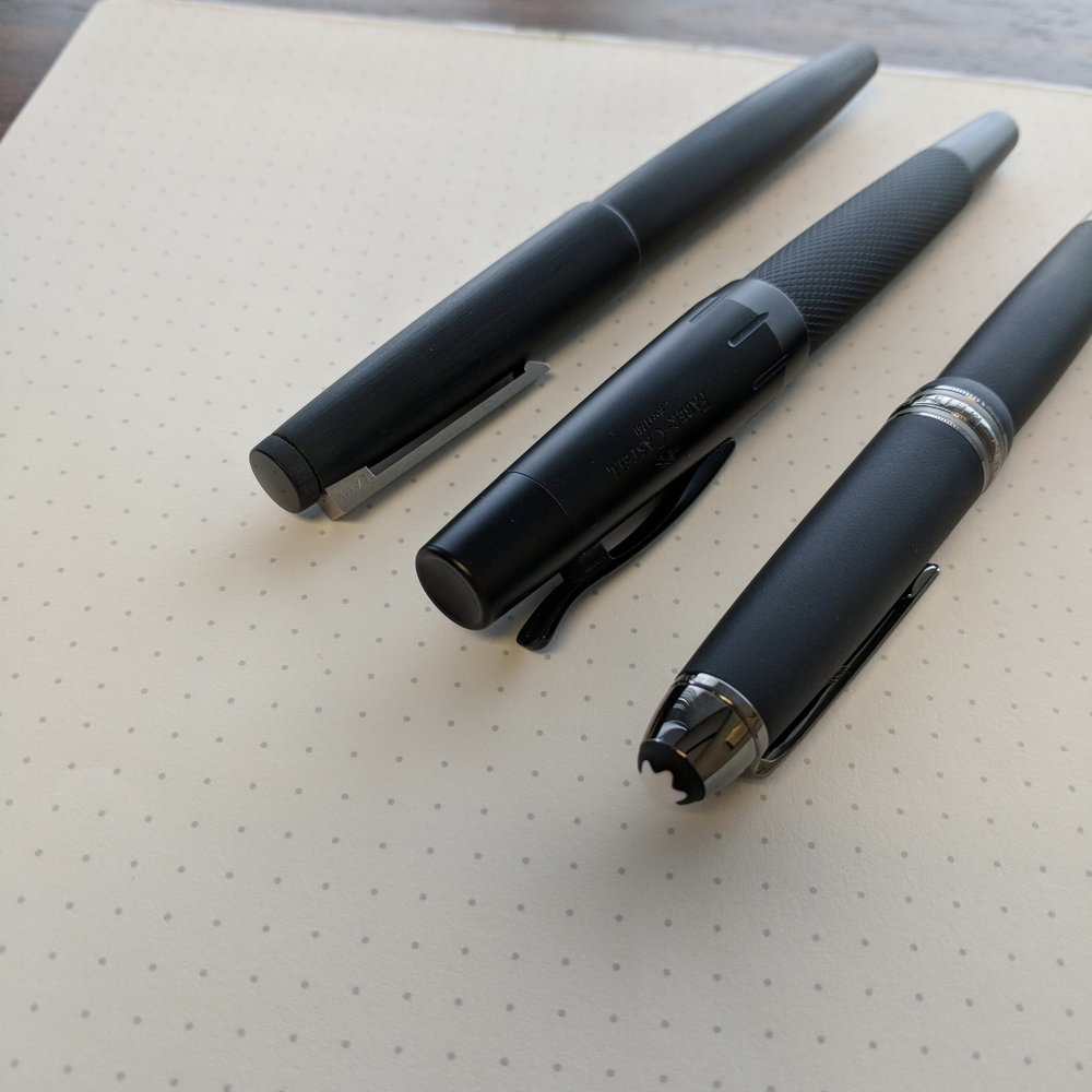 """Three """"pure black"""" workhorses, from the top: Lamy 2000, Faber-Castell E-Motion Pure Black, and Montblanc 146 Ultra Black."""
