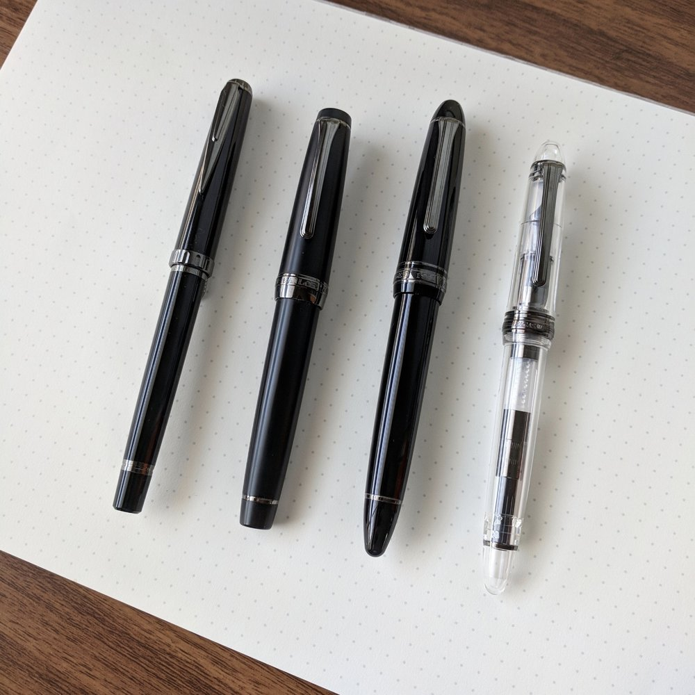 "Sailor makes several pens with black ion-plated trim. From left: Reglus ""Night Black"", Pro Gear Imperial Black, 1911 Black Luster, and 1911 Standard Demonstrator (special-edition from Nagasawa Department Store in Kobe, Japan)"