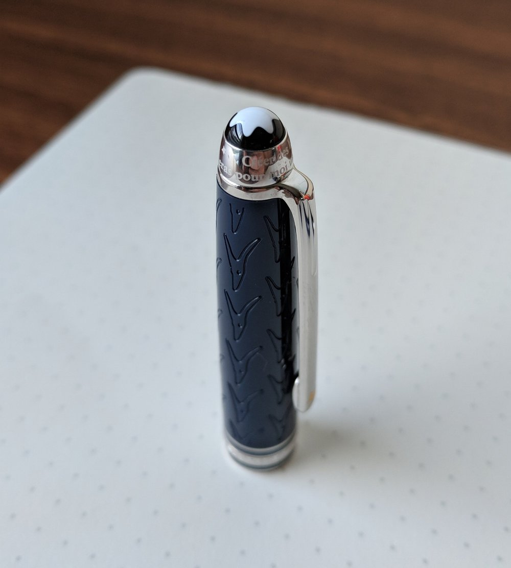 "The quote from the story is engraved around the top of the cap, just below Montblanc's signature ""snowcap"" logo. The Platinum trim complements the navy blue resin nicely."